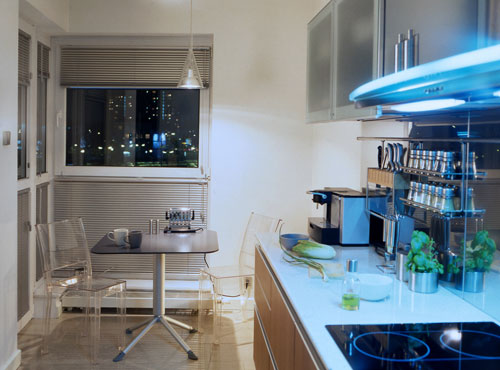 Contemporary-kitchen-with-wood-floor-small-table-glass-chairs-handing-lamps-and-blinds